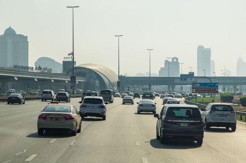 Cars on city street against clear sky