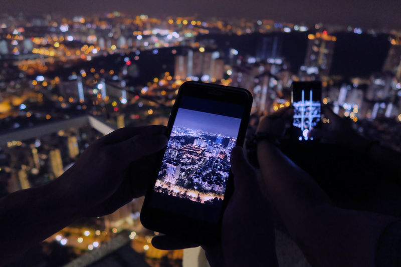 Close-up of hand holding smart phone against illuminated cityscape at night