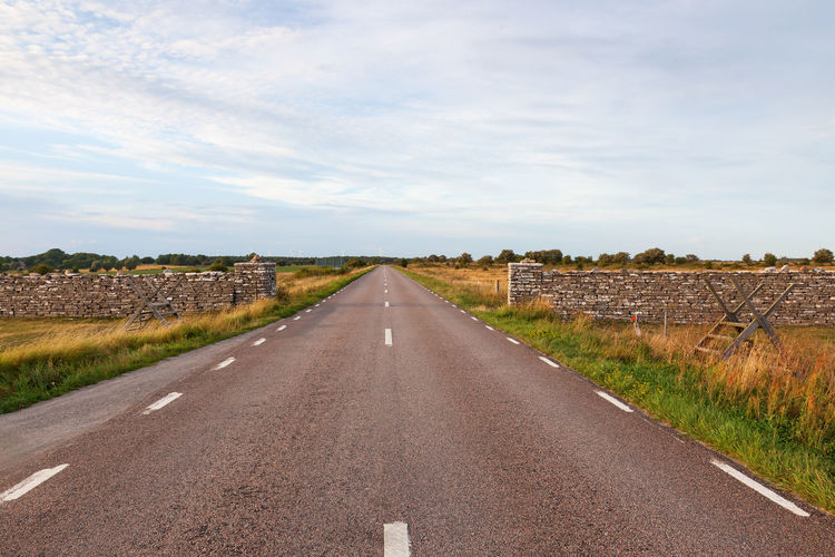 Country road straight to the horizon at the Karl X Gustavs stone wall Road Country Road Straight Horizon Sky Direction The Way Forward Nature No People Landscape Environment Cloud - Sky Land Day Tranquil Scene Scenics - Nature Outdoors Tranquility Stone Wall Meadow Moor  Field Summer Sweden Öland Travel Asphalt Country Countryside View Empty Roadways Horizon Over Land Copy Space Famous Place