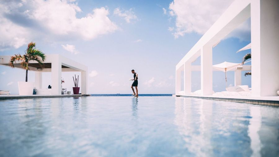 Side View Of Man Walking At Infinity Pool Against Cloudy Sky