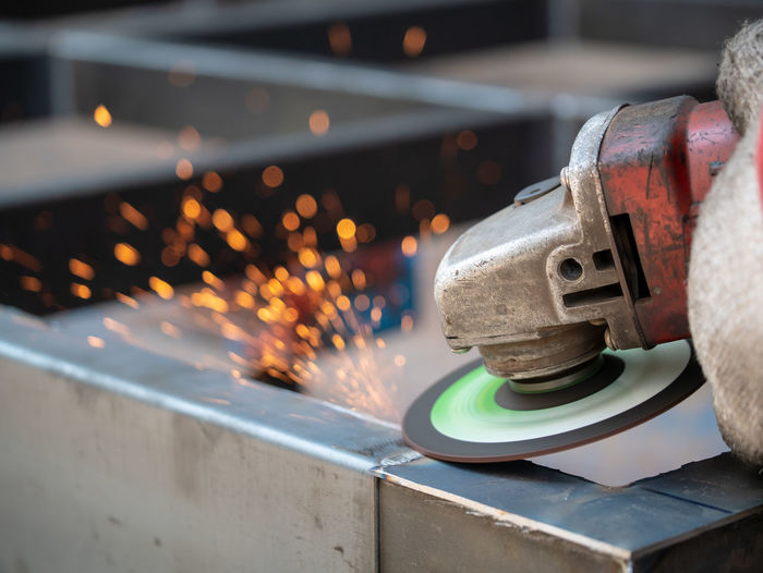 Grinder metal angle grinder with huge amount of sparks. Worker using grinder to work on piece of metal in workshops Metal Indoors  Motion Industry Close-up Heat - Temperature Technology Blurred Motion Focus On Foreground Factory Working Occupation Metal Industry Equipment Workshop Burning Sparks Fire Skill  No People Industrial Equipment Steel
