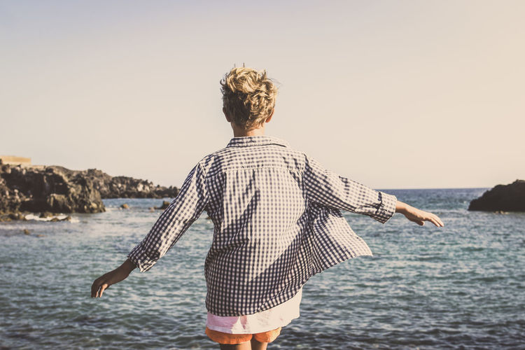 Rear view of cheerful boy standing at beach against clear sky
