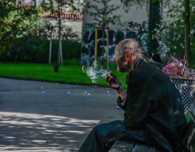 Activity Bad Habit Cigarette  Day Focus On Foreground Food And Drink Holding Leisure Activity Lifestyles Males  Men One Person Outdoors Real People Side View Sitting Smoking Issues Social Issues Three Quarter Length