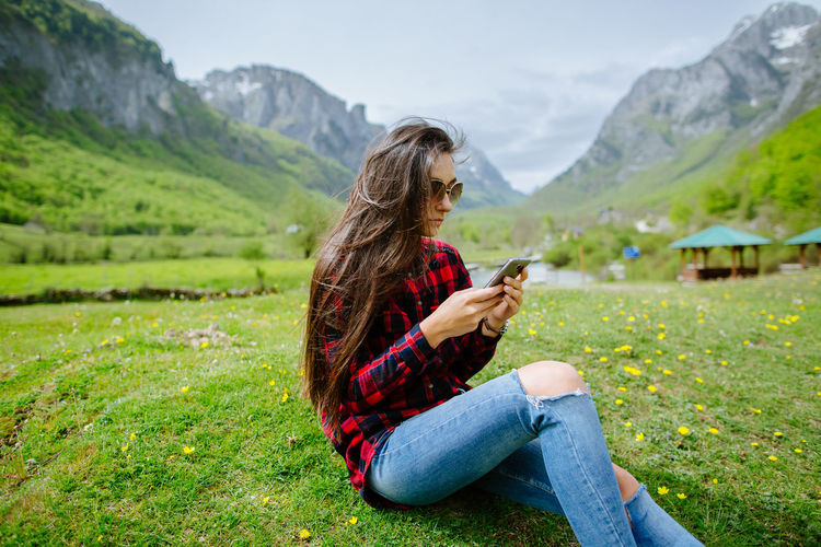 Woman using phone while sitting on grassy field against mountains