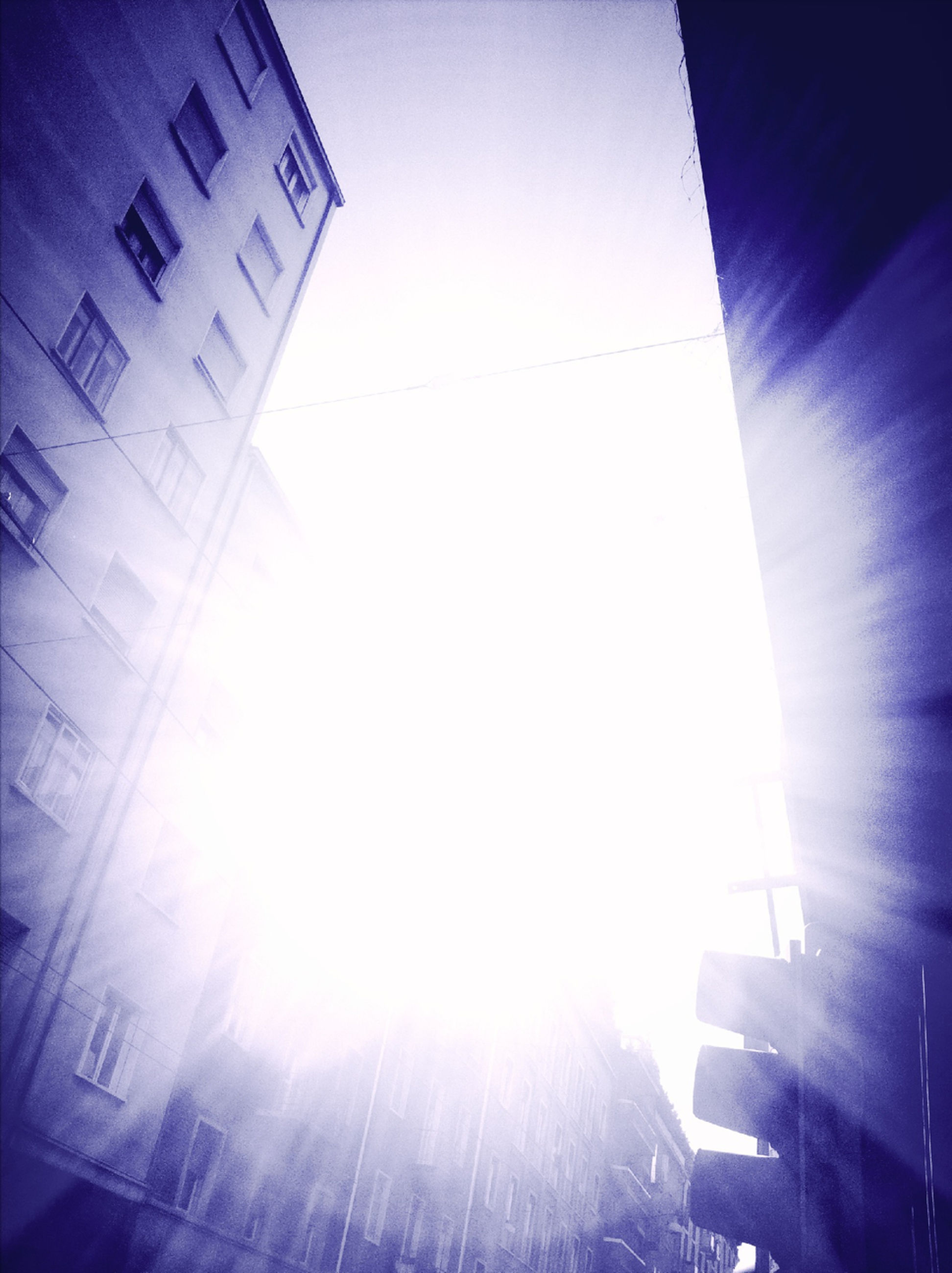 sun, sunbeam, building exterior, architecture, built structure, low angle view, lens flare, sunlight, bright, clear sky, sunny, brightly lit, sky, city, building, blue, vapor trail, day, outdoors, back lit