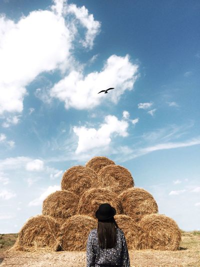 Rear view of woman standing in front of haystack against cloudy sky