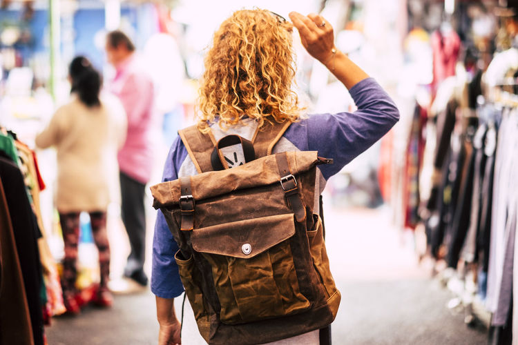 Blonde curly hair woman backpacker traveler viewed from rear at used market enjoying the shopping and alternative vacation - leather backpack view for travel concept Rear View Focus On Foreground Real People Women Adult City Street Lifestyles People Day Bag Casual Clothing Hair Carrying Hairstyle Walking Leisure Activity Backgrounds Market Dresses Clothes Curly Hair Caucasian Shopping Recycled Used Buying Searching Standing Females Vacations Outdoors Store Tourist Independence Business Consumerism