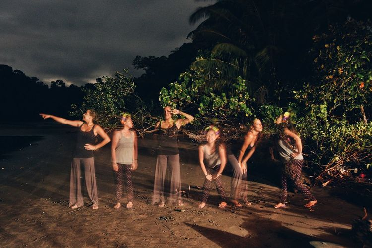 Multiple image of friends enjoying at beach against trees during night