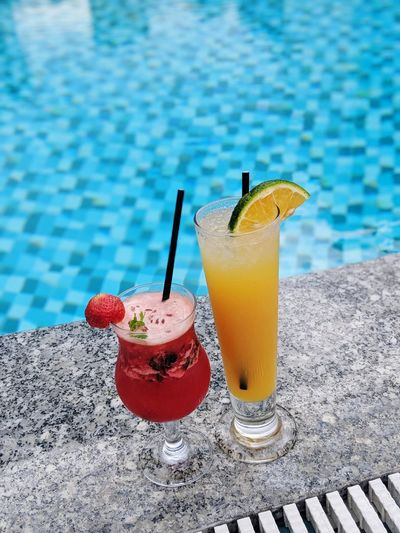 Close-up of drink on table against swimming pool