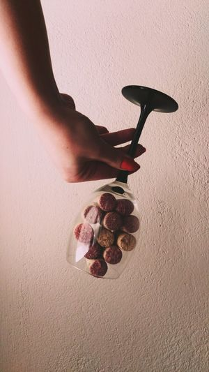 Cropped Image Of Hand Holding Wineglasses With Cork Against Wall