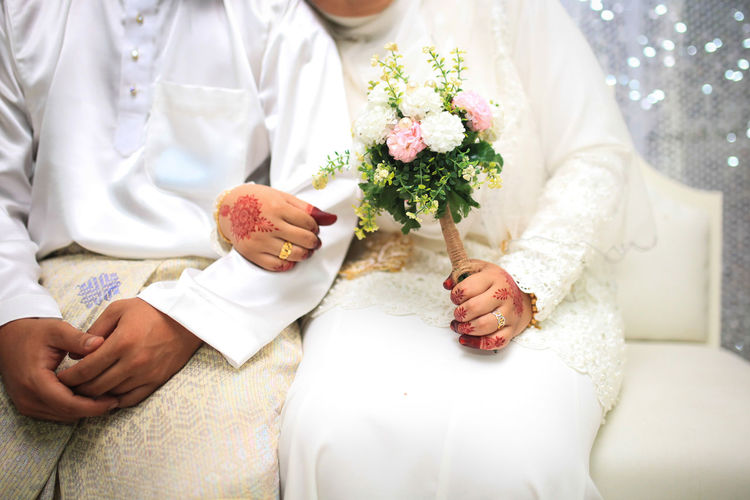 Midsection of couple with bouquet sitting on sofa during wedding ceremony