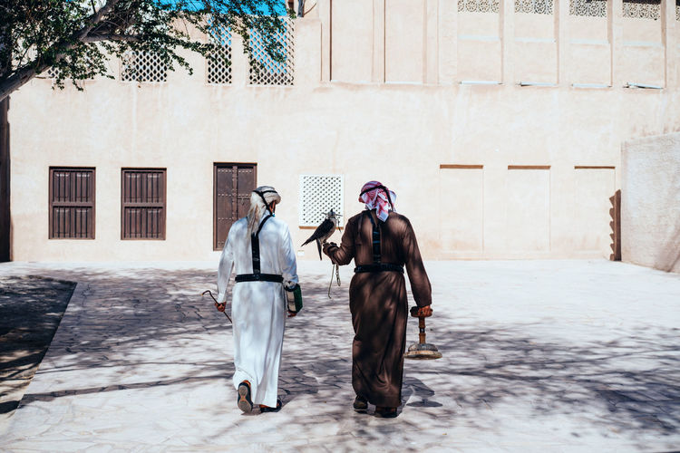 Traditionally dresses arabic man walking with a falcon next to the wind tower