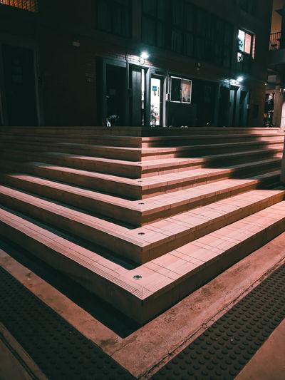 Empty seats in illuminated building at night
