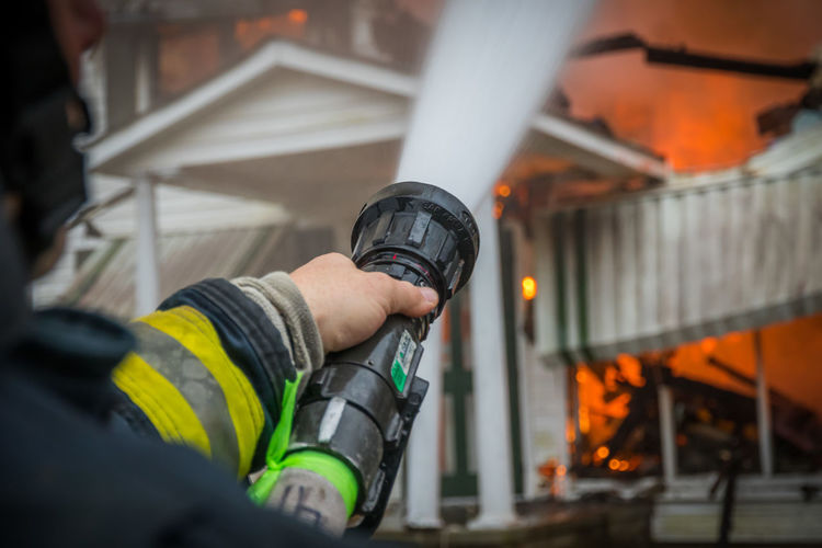 Close-Up Of A Firefighter Spraying Burning House With Hose