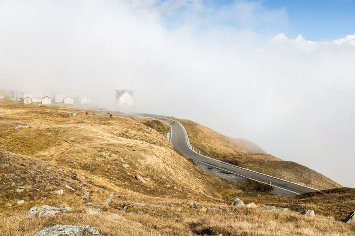 On the road on the Furka pass in the Swiss alps in Canton Uri in Switzerland Grimselpass Pastel Power Beauty In Nature Cloud - Sky Day Fog Furkapass Landscape Mountain Mountain Pass Mountain Road Nature No People On The Move Outdoors Scenics Sky Swiss Alps Switzerland Tranquil Scene Uri Winding Road