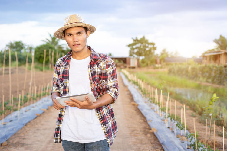 Portrait of young man wearing hat standing on field