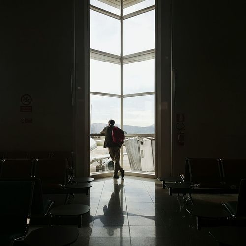 Rear view of standing by window at airport