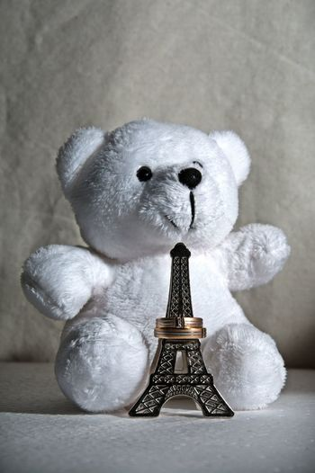 Teddy bear with replica eiffel tower against wall