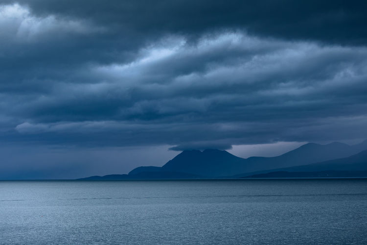 Scenic view of sea and mountain against dramatic sky