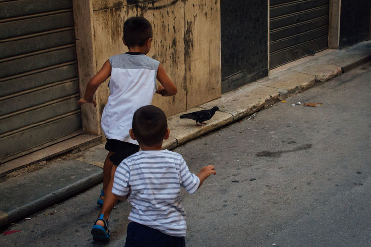 Rear view of boys playing on street