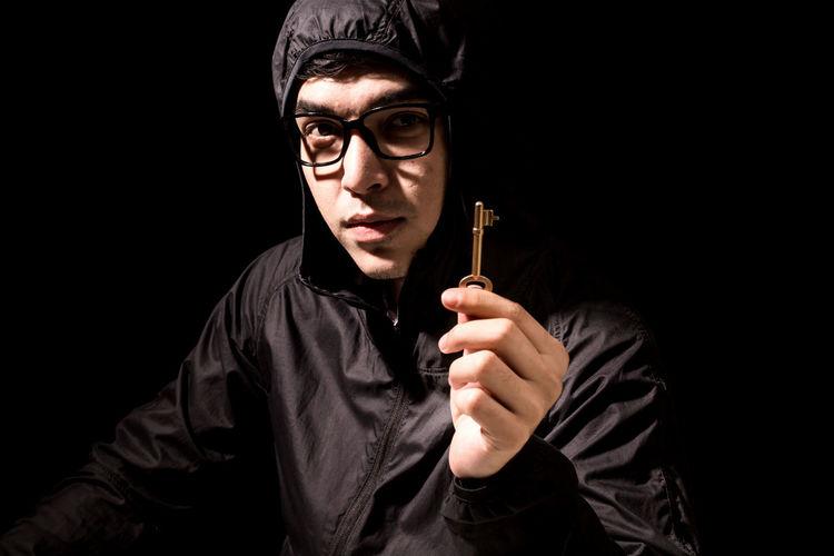 Portrait of criminal holding key against black background