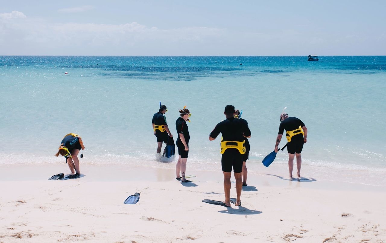 People with snorkel at beach against sky