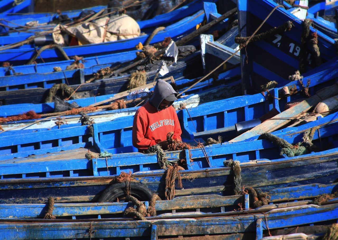 MAN WORKING ON BOAT MOORED AT BLUE SHORE