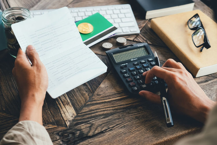 Midsection of businessman using calculator on table
