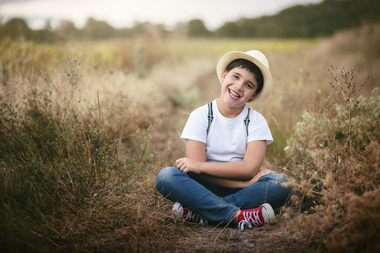 Field Fun Happy Holidays Lifestyle Nature Child Childhood Field Grass Happiness Nature Outdoors Playful Portrait Sitting Smile Smiling Spring Summer