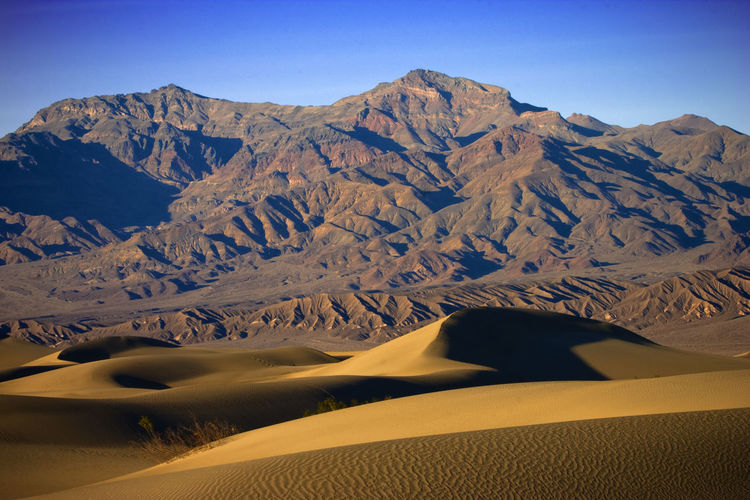 Scenic View Of Mountains And Sand Dune At Death Valley