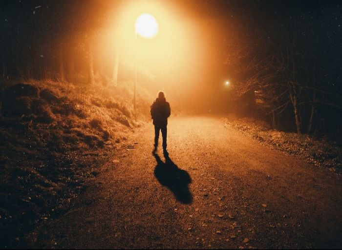 Rear view of silhouette man walking on illuminated street at night