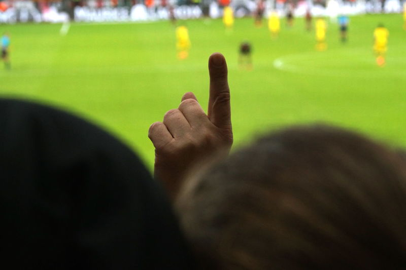 Fan making gesture while watching soccer at stadium