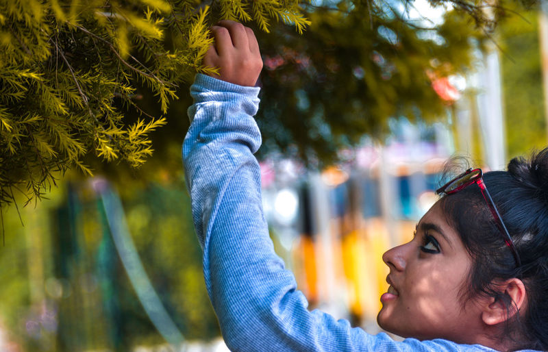 Close-up of smiling boy with hands on tree