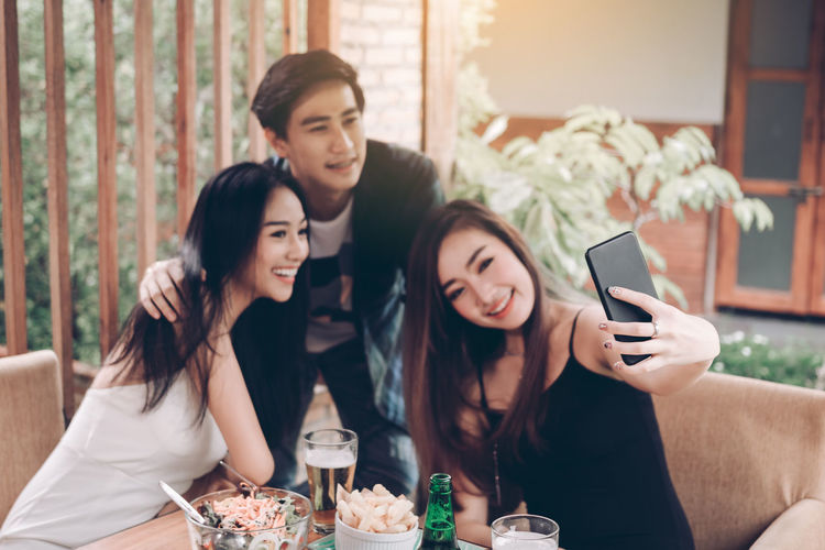 Young Woman Taking Selfie With Friends At Restaurant