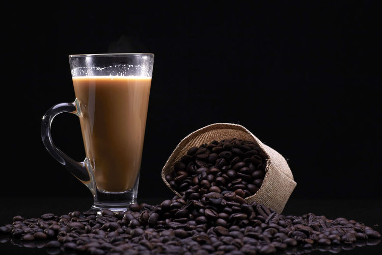 A cup of coffee with coffee beans over the black background Food And Drink Coffee - Drink Coffee Still Life Drink Refreshment Roasted Coffee Bean Indoors  Cup Coffee Cup Food Table Freshness Mug Black Background Close-up Studio Shot No People Coffee Bean Frothy Drink Glass Caffeine Crockery