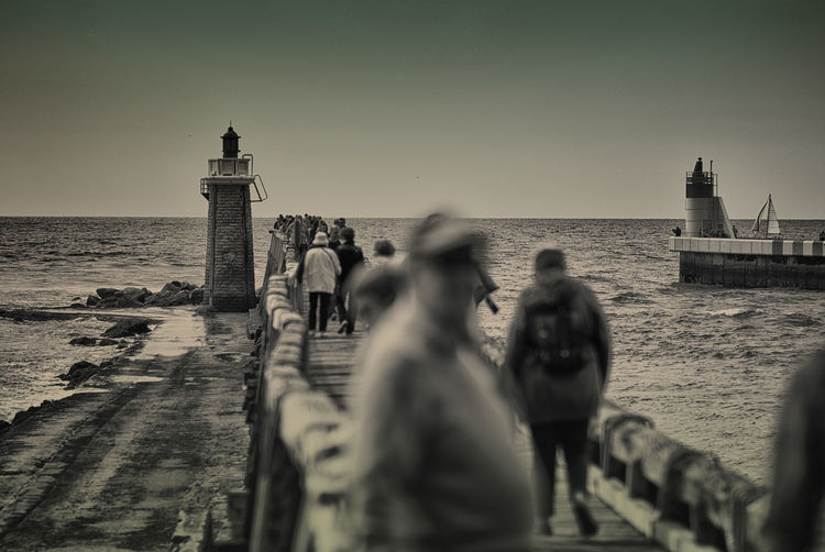 People walking on footbridge over sea by lighthouse against clear sky