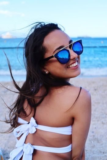 Use your smile to change the world but don't let the world change your smile. EyeEm Selects Sunglasses Real People Beach Sea One Person Beautiful Woman Young Adult Young Women Lifestyles Outdoors Vacations Leisure Activity Bikini Sand Beauty Happiness Smiling Sky Summer Water