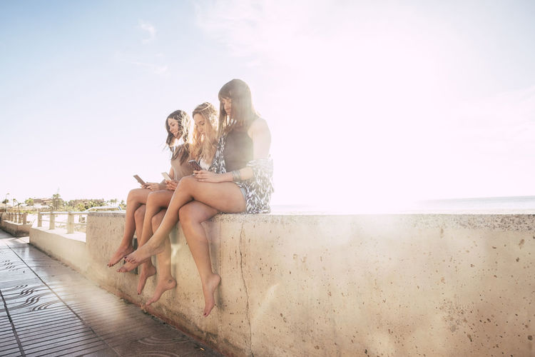 Female Friends Using Phone While Sitting On Retaining Wall Against Sky