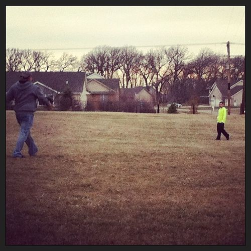 The boys playing catch with the football.