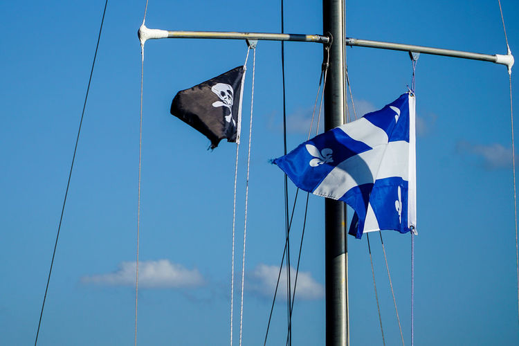 Low Angle View Of Flags Hanging On Mast Against Blue Sky