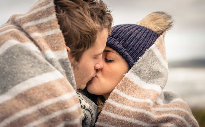 Closeup of young beautiful couple kissing under blanket in a cold day with sea and dark cloudy sky on the background Outdoors Nature Horizontal Woman Man Two People Love Winter Cold Temperature Female Male Romantic Autumn Fall Hat Scarf Clouds Meadow Togheter Boyfriend Girlfriend Blanket Happiness Embracing Kissing