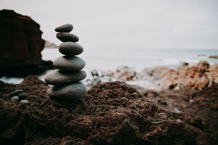 Stack of stones on rock at beach against sky