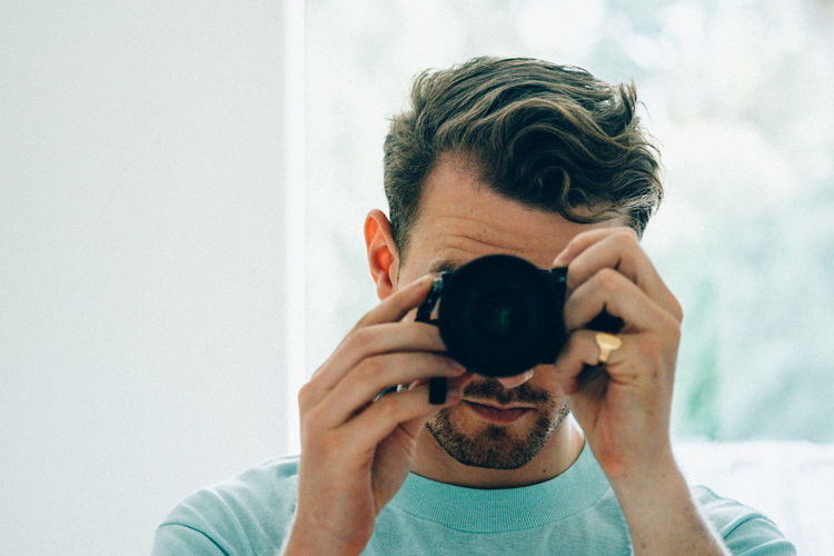 Close-up of man taking picture from camera