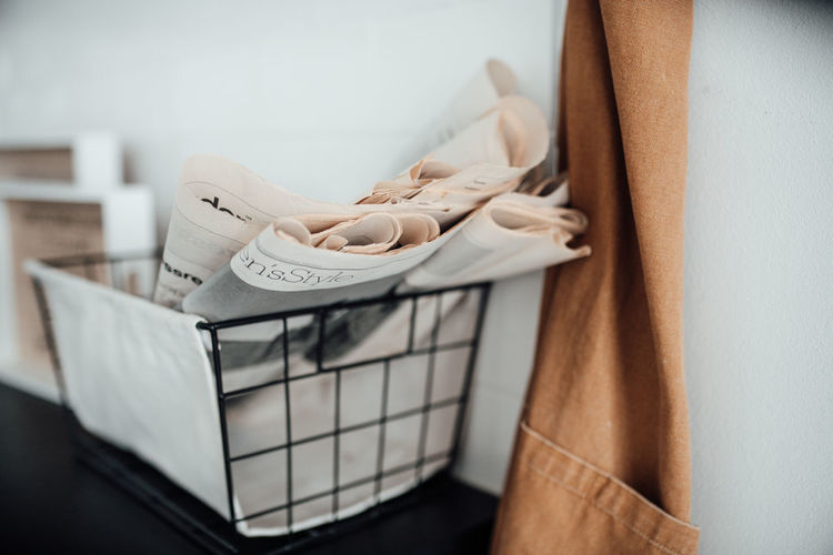 Close-up of newspaper in basket by wall at home