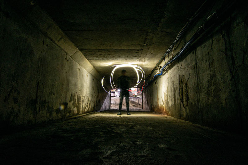 Rear view of man in illuminated tunnel