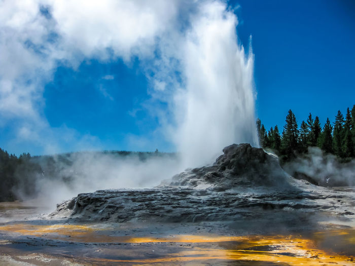 Closeup of Morning Glory Pool, a hot spring in the Upper Geyser Basin in Yellowstone National Park, Wyoming and Montana, United States. Castle Geyser erupts with hot water and steam with pools of thermophilic bacteria and is a cone geyser in the Upper Geyser Basin of Yellowstone National Park, Wyoming, United States. Dramatic view of dead trees and travertine terraces rock formations made of crystallized calcium carbonate in Mammoth Hot Springs, Yellowstone National Park in Wyoming and Montana, United States. Gaiser Grand Prismatic Lake Wyoming Landscape Yellowstone Yellowstone National Park Yellowstone National Park. Beauty In Nature Cloud - Sky Day Erupting Geology Geyser Grand Prismatic Grand Prismatic Spring Heat - Temperature Hot Spring Lake Landscape Motion Nature No People Outdoors Park Physical Geography Pool Power In Nature Scenics Sky Smoke - Physical Structure Spraying Steam Tourism Travel Travel Destinations Volcanic Landscape Vulcano Water
