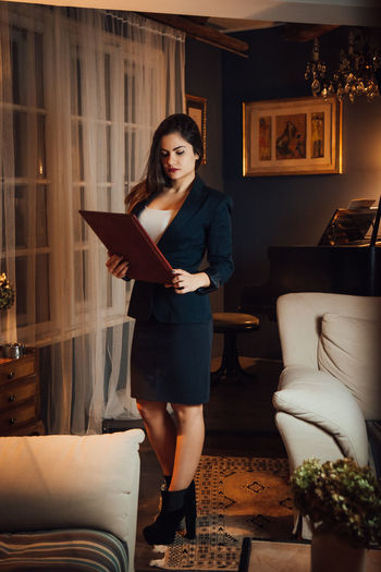 One Person Young Adult Real People Women Indoors  Holding Front View Adult Young Women Lifestyles Sofa Furniture Publication Casual Clothing Home Interior Activity Reading Book Hairstyle Beautiful Woman