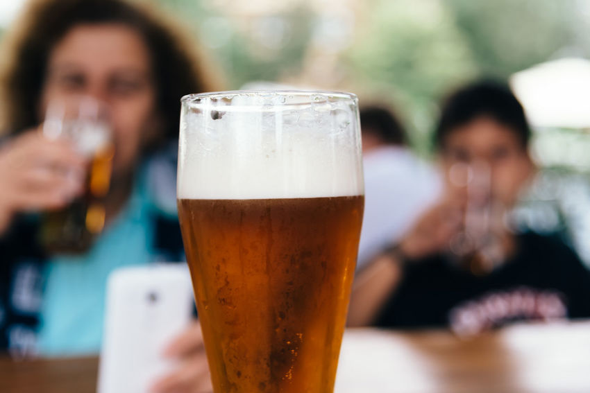 Close up of pint of lager beer against people Czech Lager Beer Adult Alcohol Beer Beer - Alcohol Beer Glass Drink Drinking Drinking Glass Focus On Foreground Food And Drink Freshness Glass Holding Household Equipment Lager Leisure Activity Lifestyles Mid Adult Real People Refreshment Table Women