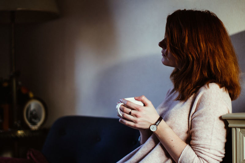 Side View Of Woman Holding Coffee Cup While Sitting On Sofa