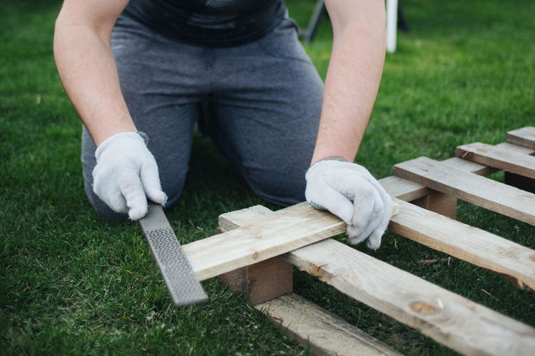 Low section of man cutting wooden plank on field